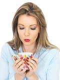 Junge Frau, die einen Becher Tee oder Kaffee trinkt Lizenzfreie Stockbilder