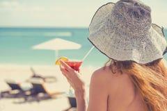 Junge Frau, die einen Bikini hält ein Cocktail genießt Meerblick trägt stockfotografie