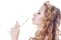 Junge Frau, die einen Champagner trinkt Stockbild