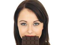 Junge Frau, die einen dunklen Schokoriegel isst Lizenzfreie Stockfotos