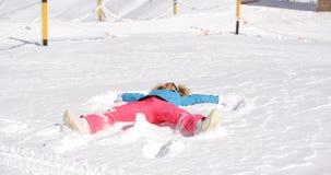 Junge Frau, die einen Engel im weißen Schnee macht Lizenzfreies Stockfoto