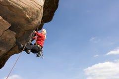 Junge Frau, die einen Felsen steigt Stockfotografie