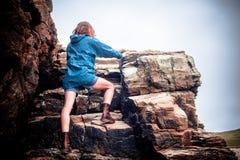 Junge Frau, die einen Felsen steigt Lizenzfreies Stockbild