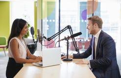 Junge Frau, die einen Gast in einem Studio für einen Podcast interviewt stockbild