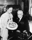 Junge Frau, die einen Geburtstagskuchen einem Mann der älteren Personen darstellt (alle dargestellten Personen sind nicht längere Stockfotografie