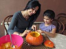 Junge Frau, die einen Halloween-Kürbis mit ihrer sieben Jährig-Tochter schnitzt Stockbild