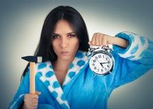 Junge Frau, die einen Hammer und einen Wecker hält Lizenzfreies Stockbild