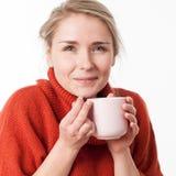 Junge Frau, die einen heißen Tee, Kaffee, Schokolade hält Lizenzfreie Stockbilder