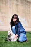 Junge Frau, die einen Hund hält lizenzfreie stockbilder