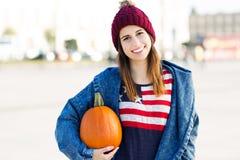 Junge Frau, die einen Kürbis hält Lizenzfreie Stockfotos