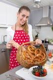 Junge Frau, die einen Korb mit frischen bayerischen Brezeln darstellt Lizenzfreie Stockfotos