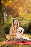 Junge Frau, die einen Labrador-Apportierhundhund umarmt Lizenzfreie Stockfotos