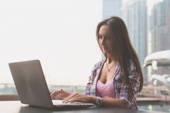 Junge Frau, die einen Laptop draußen arbeitet verwendet Weiblich, den Schirm betrachtend und auf Tastatur schreibend Stockbild