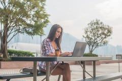 Junge Frau, die einen Laptop draußen arbeitet verwendet Weiblich, den Schirm betrachtend und auf Tastatur schreibend Stockbilder