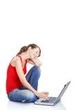 Junge Frau, die einen Laptop verwendet Lizenzfreie Stockfotos