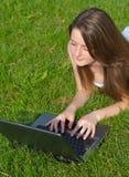 Junge Frau, die einen Laptop verwendet stockfotografie