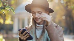 Junge Frau, die einen Mantel unter Verwendung der Smartphonestellung im Herbstpark trägt Mädchen, das die Kamera untersucht Techn stock footage