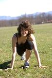 Junge Frau, die in einen Park ausdehnt Stockfotografie