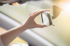 Junge Frau, die einen Rückspiegel im Auto justiert lizenzfreie stockfotos