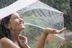 Junge Frau, die einen Regenschirm im Regen verwendet Stockbilder