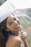 Junge Frau, die einen Regenschirm im Regen verwendet Stockfotografie