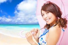Junge Frau, die einen Regenschirm mit Strandhintergrund hält Lizenzfreie Stockfotografie