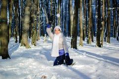 Junge Frau, die einen Schneeball spielt im schneebedeckten Park bei einem sonnigen Wetter im Winter wirft lizenzfreies stockfoto
