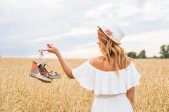 Junge Frau, die einen Schuh - Verkauf, Verbraucherschutzbewegung und Leutekonzept hält lizenzfreie stockbilder