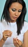 Junge Frau, die einen Schwangerschaftprüfungsstreifen liest Stockbild