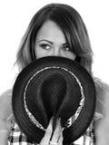 Junge Frau, die einen schwarzen Tilbury Straw Hat trägt Stockfoto