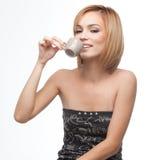 Junge Frau, die einen Sip Kaffee isst Stockfoto