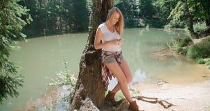 Junge Frau, die einen Smartphone in einem Wald verwendet Stockfoto