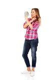 Junge Frau, die einen Spiegel hält und ihr Haar kämmt Stockfotos