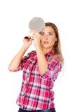 Junge Frau, die einen Spiegel hält und ihr Haar kämmt Stockbilder