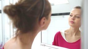 Junge Frau, die einen Spiegel poliert stock video