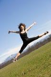 Junge Frau, die einen Sprung bildet Stockfotografie
