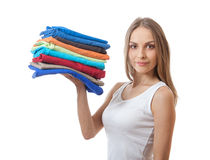 Junge Frau, die einen Stapel von Kleidung hält lizenzfreies stockbild