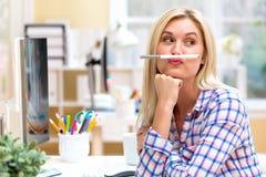 Junge Frau, die einen Stift über Lippen hält Stockbilder