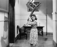 Junge Frau, die einen Stuhl über ihrem Kopf im Ärger hält (alle dargestellten Personen sind nicht längeres lebendes und kein Zust Stockfoto