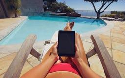 Junge Frau, die einen Tablet-PC nahe dem Pool verwendet Stockfoto