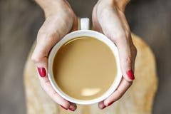 Junge Frau, die einen Tasse Kaffee in ihren Händen hält Stockbilder