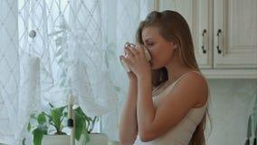 Junge Frau, die einen Tasse Kaffee in ihrer Küche hält stock video