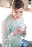 Junge Frau, die einen Tasse Kaffee lächelt und genießt Lizenzfreies Stockbild