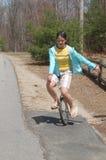 Junge Frau, die einen Unicycle herauf eine Wohnstraße reitet Lizenzfreie Stockfotos