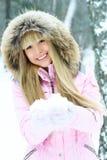 Junge Frau, die einen Weg im Winterwald hat Stockfoto