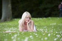 Junge Frau, die in einer Rasenfläche mit Gänseblümchen liegt Stockbild