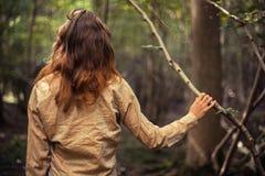 Junge Frau, die in einer Reinigung des Waldes steht Stockfotos