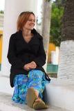 Junge Frau, die an einer Spalte sitzt Stockfoto