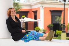 Junge Frau, die an einer Spalte sitzt Lizenzfreie Stockbilder