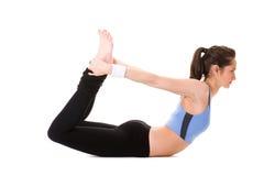 Junge Frau, die einige Übungen auf weißem Fußboden tut Stockfotos